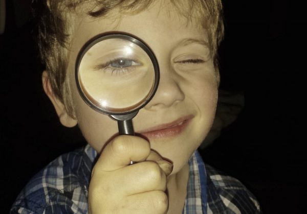 Investigating Inventions – Child looks through Magnifying glass