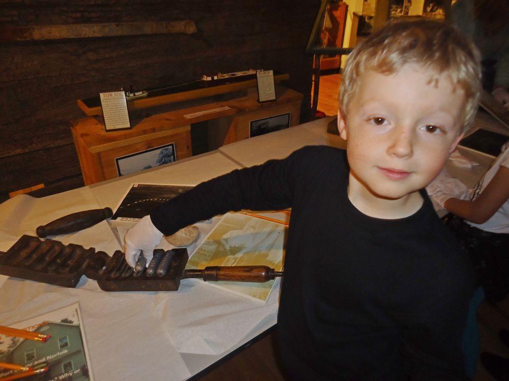 Sailing Through Time – Child holding artifact